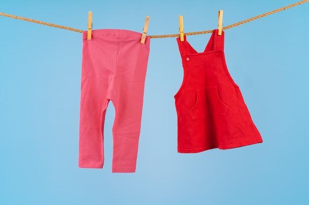 Babymeisjeskleding vastgemaakt aan een waslijn tegen blauwe achtergrond
