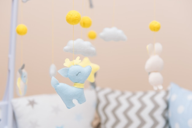 Babymobiel met verschillend speelgoed in de vorm van dieren en sterren, vilten speelgoed in wieg