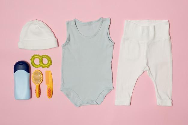 Babymode op een roze. kleding en accessoires voor verzorging.