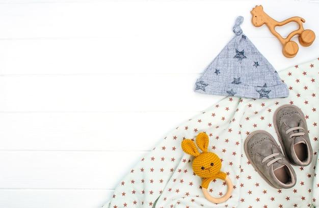 Babymuts, slofjes en houten speelgoed op witte houten