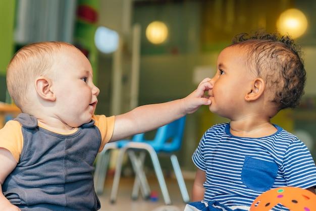 Babys die samen in de kleuterschool spelen.