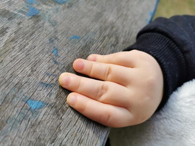 Babys hand met een vintage houten plank.