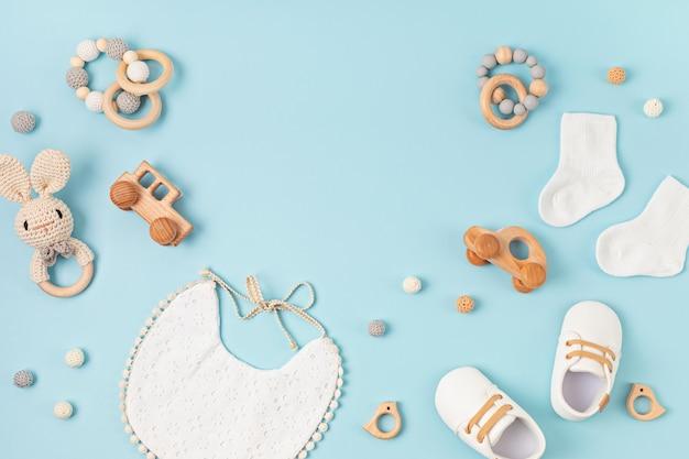 Babyschoenen, slabbetje en bijtring op pastelachtergrond. biologische pasgeboren accessoires, branding, idee voor een klein bedrijf. baby shower uitnodiging, wenskaart. platliggend, bovenaanzicht