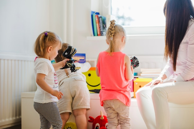 Babysitter kijken naar kinderen spelen