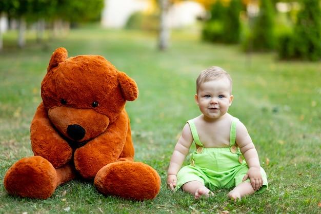 Babysitting op groen grasgazon in de zomer met grote teddybeer