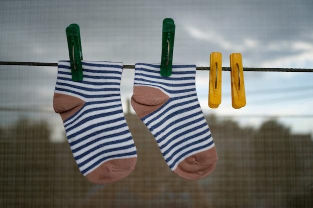 Babysokjes na het wassen aan een touwtje met kleurrijke wasknijpers