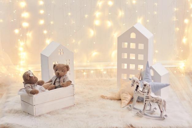Babyspeelgoed en stuk speelgoed huis op een achtergrond van kerstmislichten. vakantie inrichting