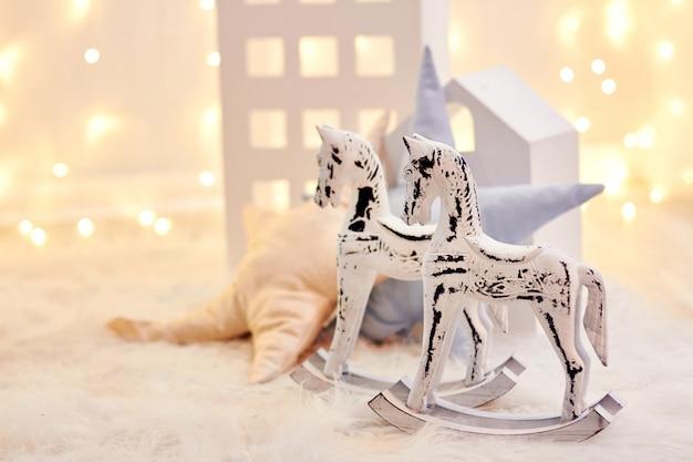 Babyspeelgoed en stuk speelgoed huis op een achtergrond van kerstmislichten. vakantiedecor, kinderkamer
