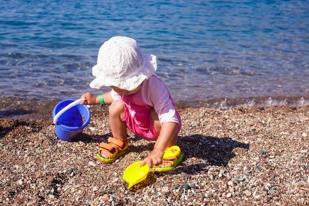 Babyspel aan de kust met rebbels en emmer