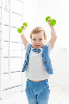 Babysporten thuis, schattige jongen tilt halters op, het concept van sport en de gezondheid van kinderen Premium Foto