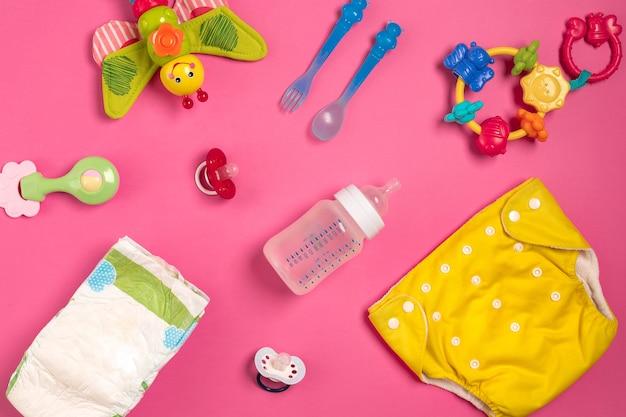 Babyverzorgingsaccessoires en luiers op roze achtergrond. bovenaanzicht. ruimte kopiëren. stilleven. plat leggen