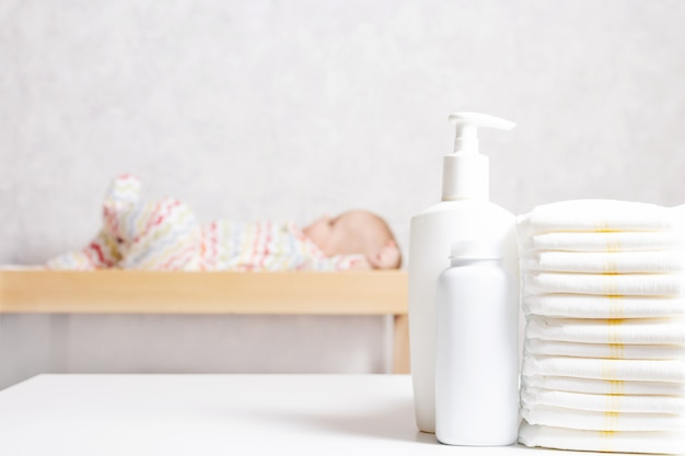 Babyverzorgingsproducten voor baby's. lotion, poeder en luiers op commode in de kinderkamer. baby cosmetica en hygiëne concept.