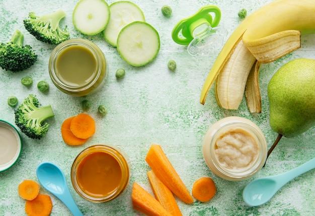Babyvoeding, assortiment van fruit- en groentepuree, plat leggen, bovenaanzicht, ruimte voor tekst