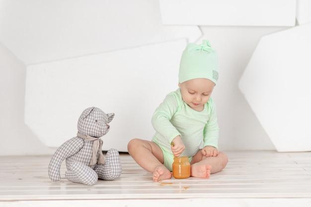 Babyvoeding lepel speelgoed in groene romper, voeding en babyvoeding concept