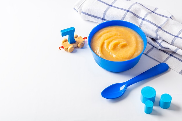 Babyvoedsel. verse zelfgemaakte appelmoes. blauwe kom met fruitpuree op stof en kinderspeelgoed op tafel. het concept van goede voeding en gezond eten. biologisch en vegetarisch eten. ruimte voor tekst kopiëren