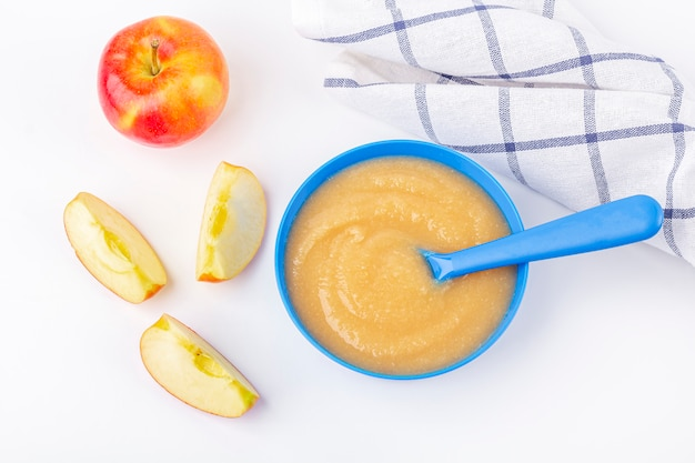 Babyvoedsel. verse zelfgemaakte appelmoes. blauwe kom met vruchtenmoes op stof en gesneden appels op tafel. het concept van goede voeding en gezond eten. biologisch en vegetarisch eten. kopieer ruimte voor tekst