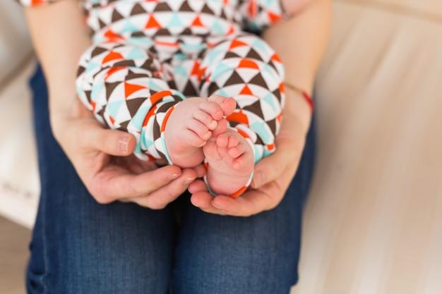 Babyvoet in vrouwelijke handen, close-up. schattige kleine jongen been. moederschap, liefde, zorg, nieuw leven concept.