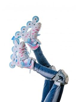 Babyvoeten in jeans en rolschaatsen die op witte achtergrond worden geïsoleerd.