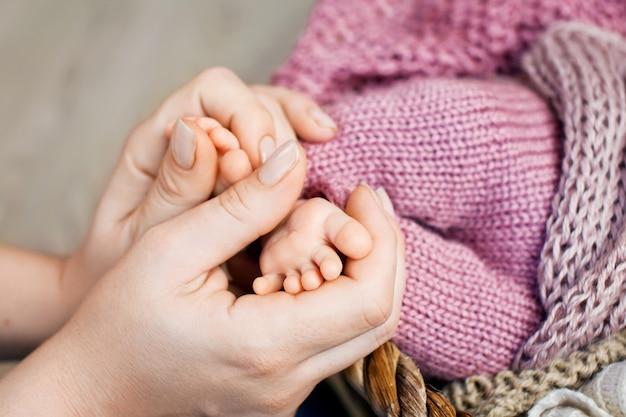 Babyvoeten in moederhanden. de voeten van de uiterst kleine pasgeboren baby op vrouwelijke gevormde handenclose-up. moeder en haar kind. gelukkig gezin concept. mooi conceptueel beeld van moederschap