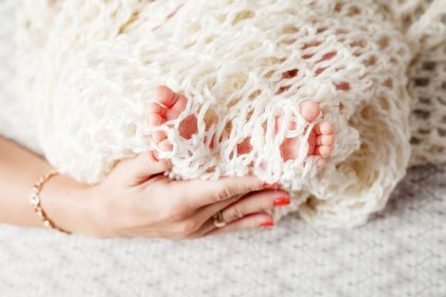 Babyvoeten in moederhanden. de voeten van de uiterst kleine pasgeboren baby op vrouwelijke gevormde handenclose-up. moeder en haar kind. mooi conceptueel beeld van moederschap