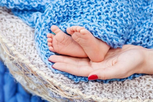 Babyvoeten in moederhanden.
