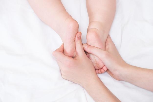 Babyvoetjes in mama's handen. de voeten van een uiterst kleine pasgeboren baby op een vrouwelijke handvorm sluiten omhoog. moeder en haar kind.