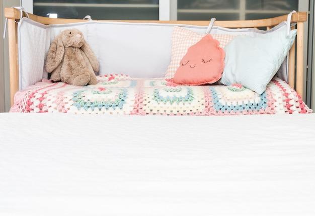 Babywieg met kussens voor kinderen en speelgoed.