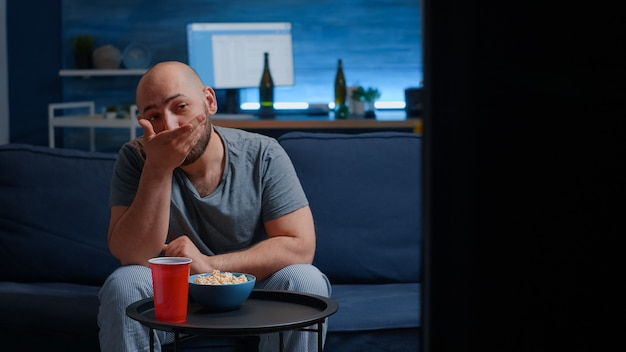 Bachelor man geniet van weekend rusten mager zittend op een comfortabele bank in de woonkamer alleen popcorn eten...