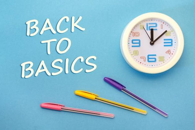 Back to basics - belettering op een blauwe achtergrond, klok en pennen