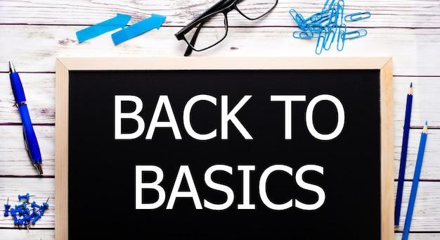 Back to basics geschreven op een zwart notitiebord naast blauwe paperclips, potloden en een pen.