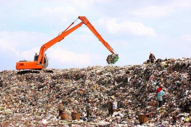 Backhoe bezig met vuilnisbelt in stortplaats. mensen die werken op de stortplaats.
