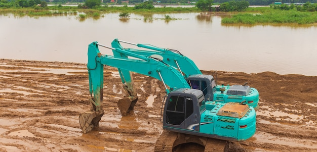 Backhoe graven van de grond om een rivierweg langs de rivier te bouwen.