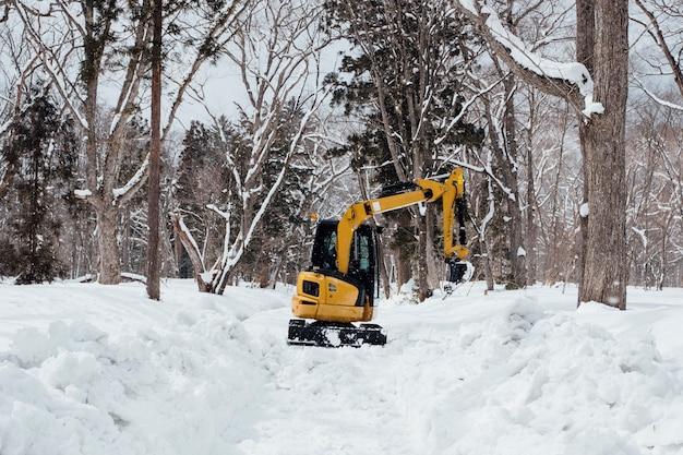 Backhoe in sneeuw bij togakushi-heiligdom, japan