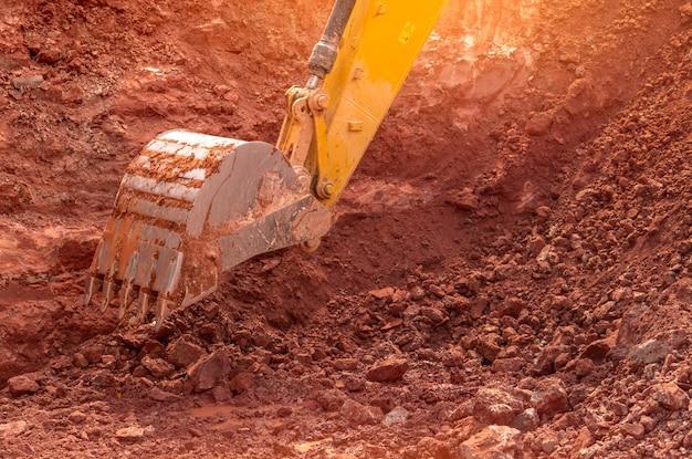 Backhoe werken door grond te graven op de bouwplaats. emmer van backhoe gravende grond. rupsgraafmachine die op vuil graaft. close-up backhoe emmer van gele backhoe. grondverzet. graafmachine.
