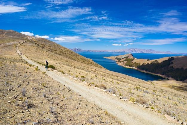 Backpacker die de majestueuze inca trails op het eiland van de zon, het titicacameer, een van de meest schilderachtige reisbestemmingen in bolivia verkent. reisavonturen en vakanties in amerika.