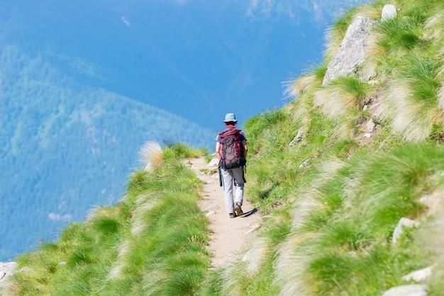 Backpacker die op wandelingssleep in de berg loopt. zomeravonturen in de alpen