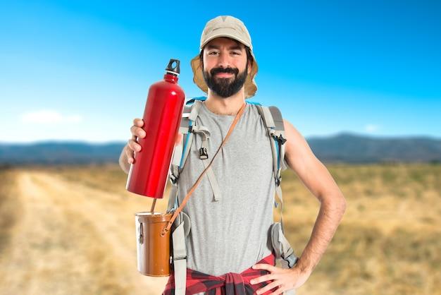Backpacker drinkwater op witte achtergrond