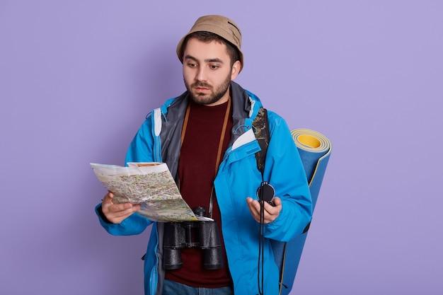 Backpacker kaart lezen op reis terwijl poseren geïsoleerd op lila achtergrond