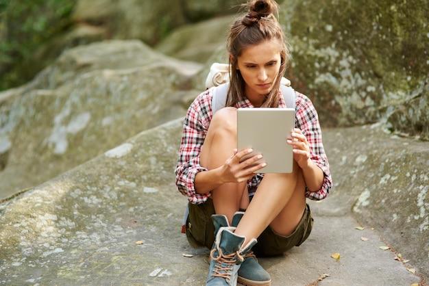 Backpacker met een tablet in de bergen