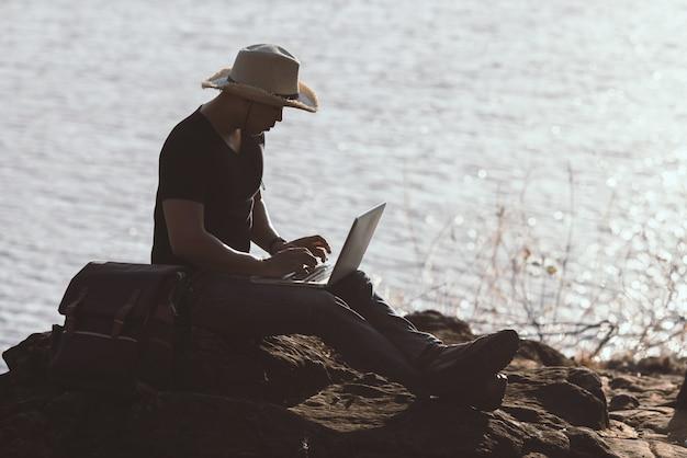 Backpacker ontspannen op de berg met behulp van laptop