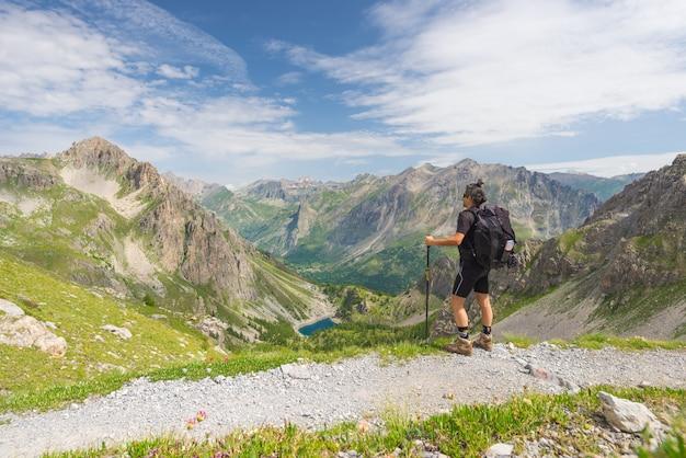 Backpacker wandelen op voetpad en kijken naar weids uitzicht vanaf de top