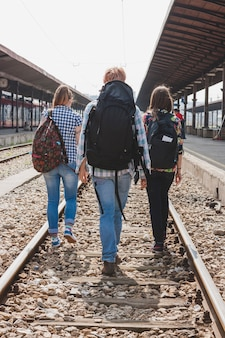 Backpackers lopen op treinsporen