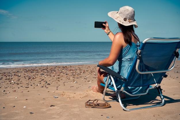 Backshot van een jonge vrouw die in bed zit en de foto maakt van de se