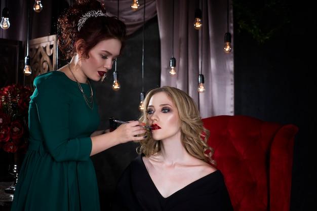 Backstage scene make-up artiest past lippenstift toe voor de fotoshoot, mooie vrouw gezicht, perfecte make-up, luxe interieur