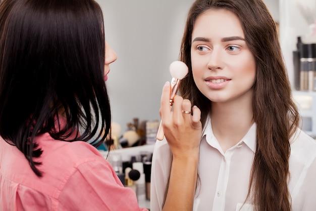 Backstage scène: professionele make-up artiest make-up voor jonge zakenvrouw in schoonheidssalon. detailopname