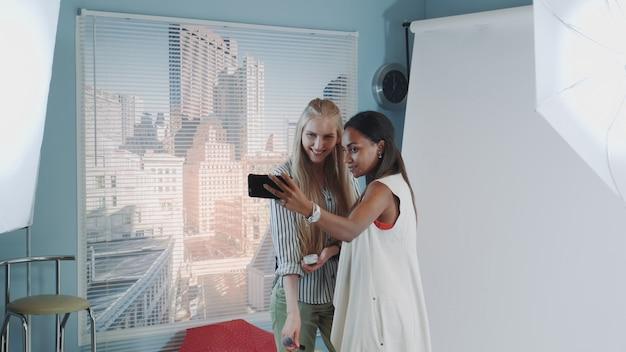 Backstage van de fotoshoot: aantrekkelijke zwarte model makende selfie met mooie visagist.
