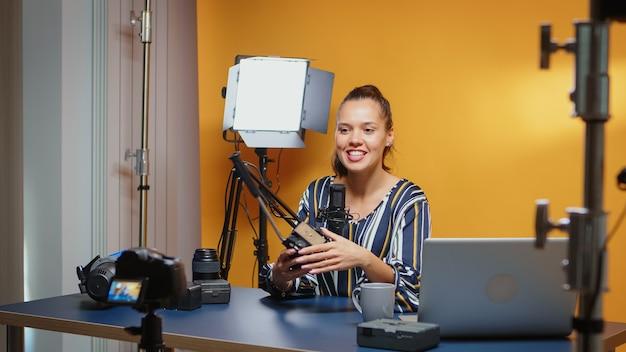 Backstage van vlogger-opname naar de camera-tutorial over fluid heads in professionele studio. influencer die online internetcontent maakt over videoapparatuur voor webabonnees en distributie, di