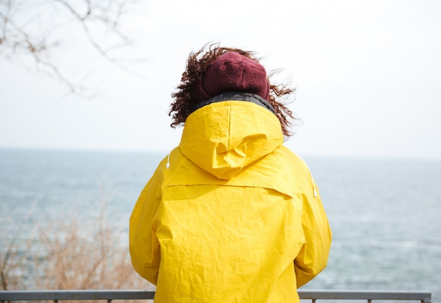 Backview schot van vrouw die weg op zee in gele regenjas kijkt