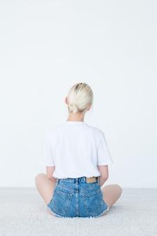 Backview van een vrouw die op de vloer zit die onzichtbaar voorwerp op wit bekijkt