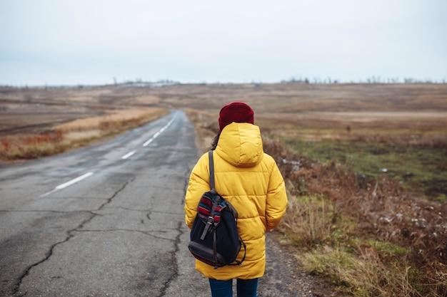 Backview van een vrouwelijke toerist met een rugzak die gele jas en rode hoed draagt, loopt op de weg.